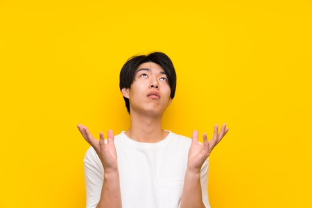 Asian man over isolated yellow wall frustrated by a bad situation