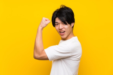 Asian man over isolated yellow wall doing strong gesture