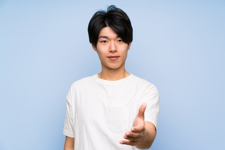 Asian man on isolated blue background handshaking after good deal Stock Photo