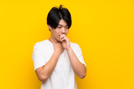 Asian man over isolated yellow wall is suffering with cough and feeling bad 免版税图像
