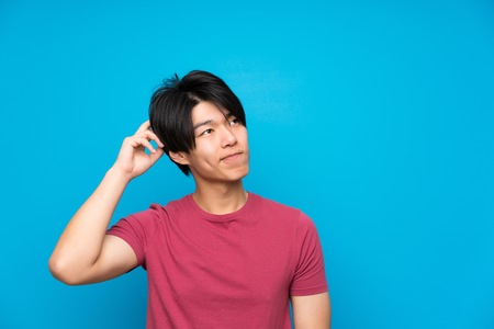 Asian man with red shirt over isolated blue wall having doubts and with confuse face expression