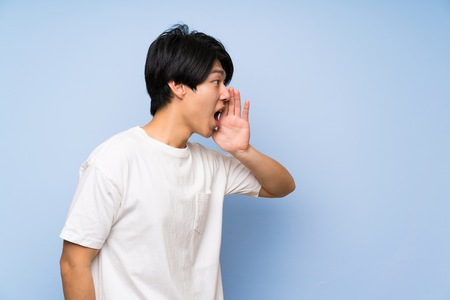 Asian man on isolated blue background shouting with mouth wide open