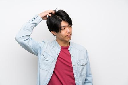 Asiatischer Mann auf isoliertem weißem Hintergrund, der beim Kopfkratzen Zweifel hat Standard-Bild