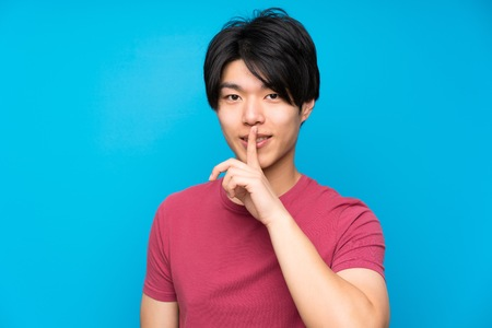 Asian man with red shirt over isolated blue wall doing silence gesture