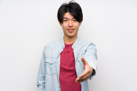 Asian man on isolated white background shaking hands for closing a good deal