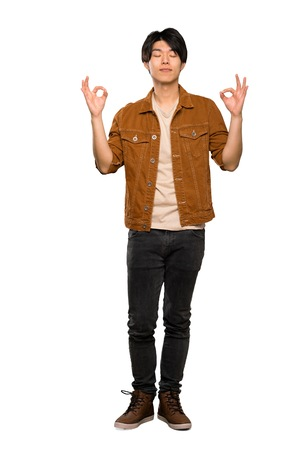 A full-length shot of a Asian man with brown jacket in zen pose over isolated white background