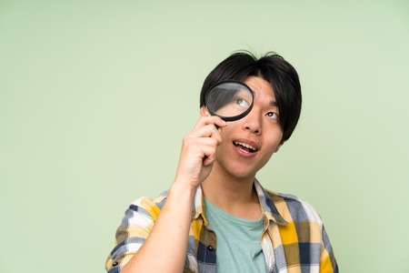 Asian man over isolated green wall holding a magnifying glass