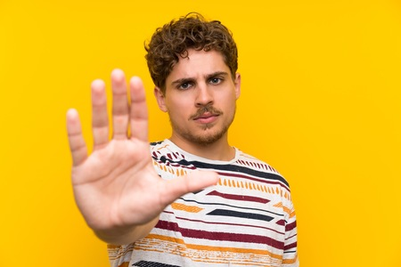 Blonde man over yellow wall making stop gesture with her hand