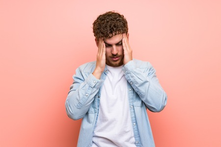 Blonde man over pink wall unhappy and frustrated with something