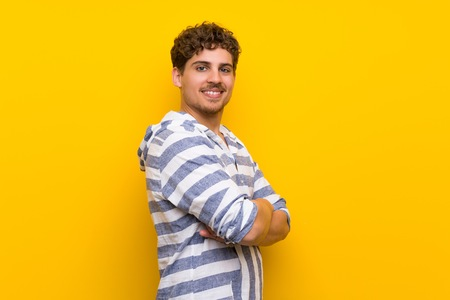 Blonde man over yellow wall keeping the arms crossed in lateral position while smiling