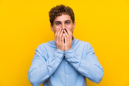 Blonde man over isolated yellow wall with surprise facial expression