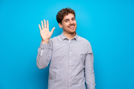 Blonde man over blue wall saluting with hand with happy expression Archivio Fotografico