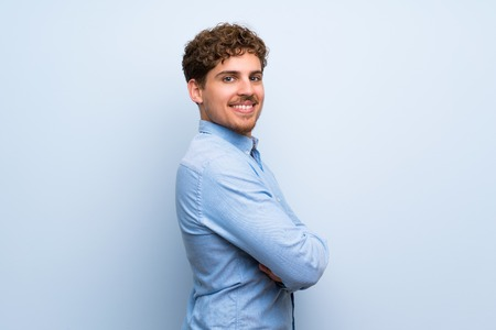 Blonde man over blue wall with arms crossed and looking forward
