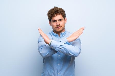 Blonde man over blue wall making NO gesture Stok Fotoğraf