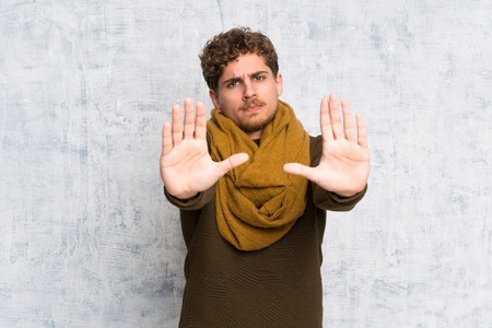 Blonde man over grunge wall making stop gesture and disappointed