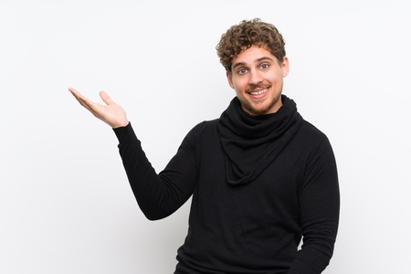 Blonde man over isolated white wall extending hands to the side for inviting to come