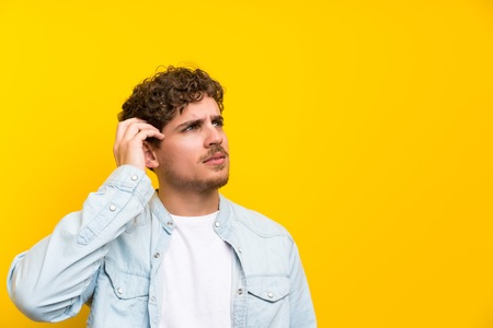 Blonde man over isolated yellow wall having doubts and with confuse face expression