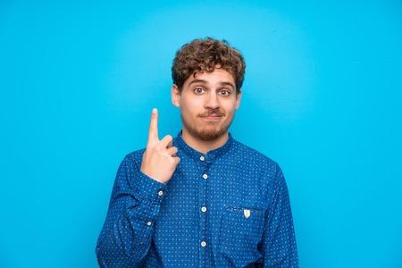 검지 손가락으로 가리키는 고립된 파란색 벽 위에 금발 남자 좋은 아이디어 스톡 콘텐츠