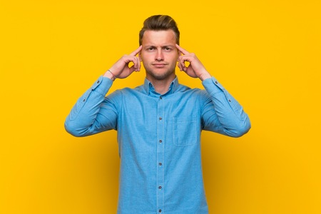 Blonde man over isolated yellow wall having doubts and thinking