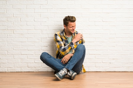 Blonde man sitting on the floor suffering from pain in shoulder for having made an effort