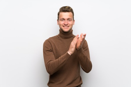 Blonde man over isolated white wall applauding after presentation in a conference Фото со стока