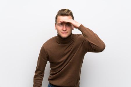Hombre rubio sobre pared blanca aislada mirando lejos con la mano para mirar algo
