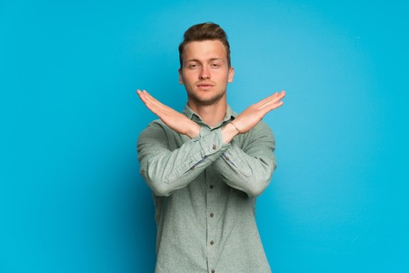 Blonde man over isolated blue wall making NO gesture