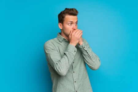 Blonde man over isolated blue wall covering mouth and looking to the side