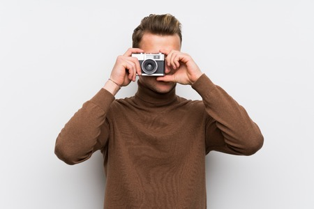 Blonde man over isolated white wall holding a camera