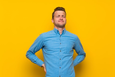 Blonde man over isolated yellow wall suffering from backache for having made an effort