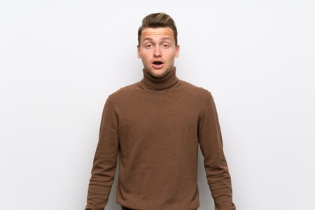 Blonde man over isolated white wall with surprise and shocked facial expression