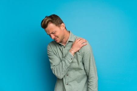 Blonde man over isolated blue wall suffering from pain in shoulder for having made an effort