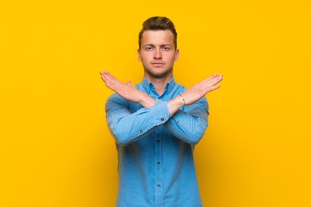 Blonde man over isolated yellow wall making NO gesture