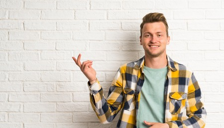 Blonde handsome man over white brick wall pointing with the index finger a great idea