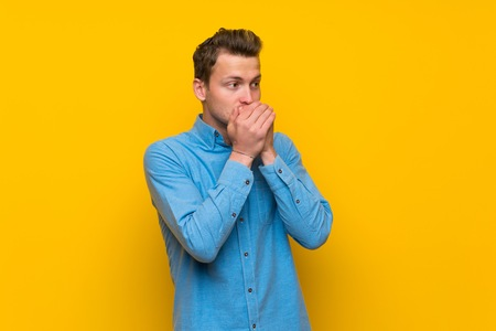 Blonde man over isolated yellow wall covering mouth and looking to the side Stock Photo