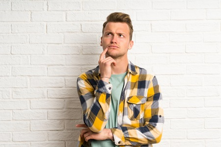 Blonde handsome man over white brick wall having doubts and with confuse face expression