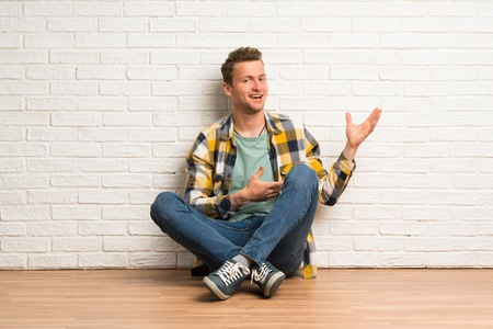 Blonde man sitting on the floor extending hands to the side for inviting to come Banco de Imagens