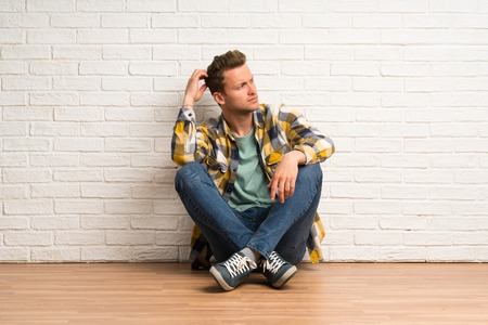 Blonde man sitting on the floor having doubts while scratching head