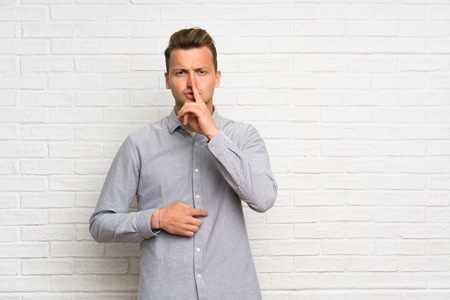 Blonde man over white brick wall showing a sign of silence gesture putting finger in mouth Archivio Fotografico