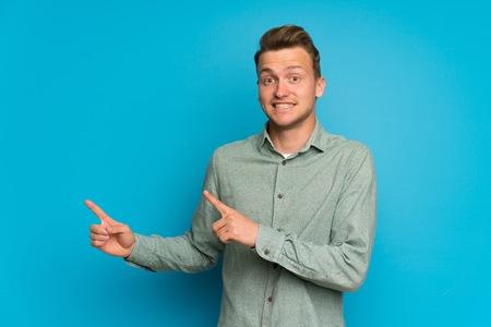 Hombre rubio sobre pared azul aislada asustado y apuntando hacia el lado Foto de archivo