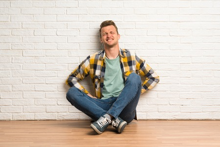 Blonde man sitting on the floor suffering from backache for having made an effort