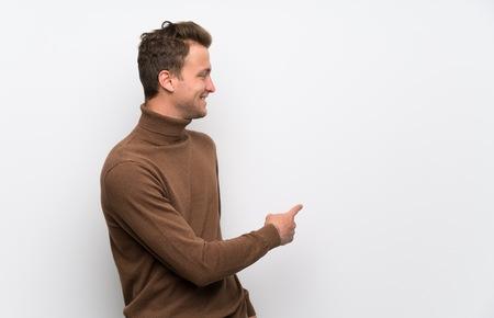 Blonder Mann über isolierter weißer Wand, der mit dem Zeigefinger nach hinten zeigt