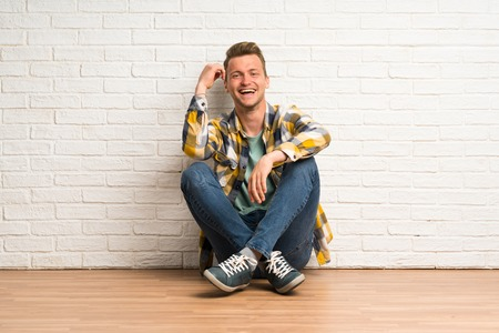 Blonde man sitting on the floor laughing