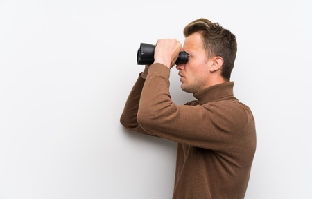 Blonde man over isolated white wall and looking in the distance with binoculars Banque d'images - 124322622