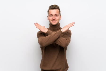 Blonde man over isolated white wall making NO gesture