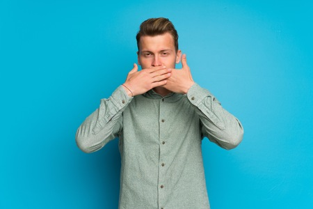Blonde man over isolated blue wall covering mouth with hands