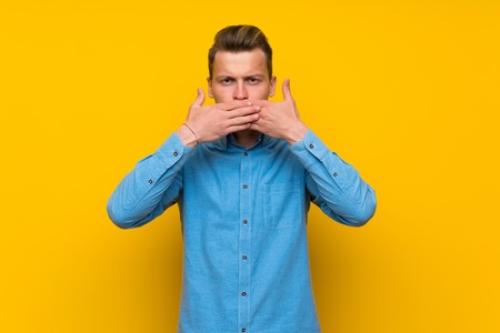 Blonde man over isolated yellow wall covering mouth with hands