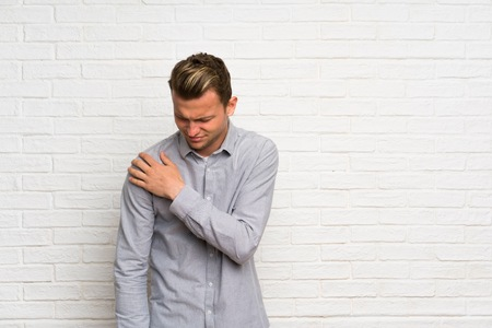 Blonde man over white brick wall suffering from pain in shoulder for having made an effort Stock fotó