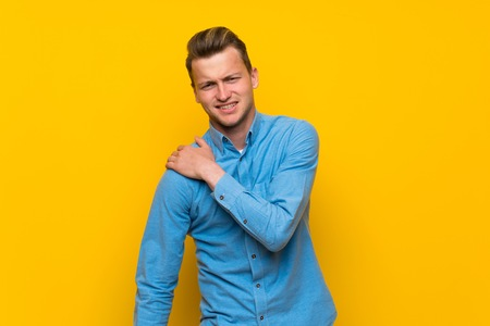 Blonde man over isolated yellow wall suffering from pain in shoulder for having made an effort