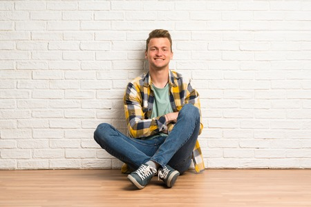 Blonde man sitting on the floor with arms crossed and looking forward